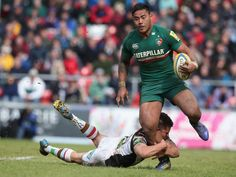 Manu Tuilagi of Leicester is held by Ben Botica during the Aviva Premiership semi final match between Leicester Tigers and Harlequins at Welford Road on May 11, 2013 in Leicester, England.