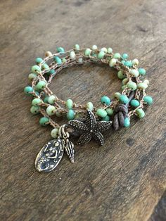 Beautiful petite blue, turquoise and white Czech beads are crocheted onto sand colored nylon cord featuring a stunning antiqued starfish button clasp and distressed leather loop. A beautiful mermaid and spindle shell dangle adding to the beauty as well as a lovely trio of beach