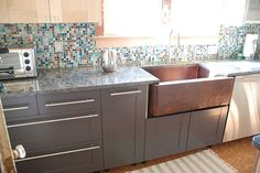 love the copper sink with the dark grey cabinets...and the backsplash ties the color together