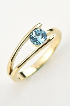 This is a yellow gold and aquamarine engagement ring designed and made by Scottish designer and goldsmith Christine Sadler