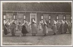 Groep meisjes in Walcherse streekdracht, spelende een kringspel op straat.