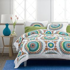 Handcrafted quilt featuring vibrant mosaics that pop against the white ground, inspired by Spanish tiles. Shop quilts at The Company Store.