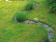 This flowing S-curved bed can extend the route through a yard, and trick the eye into thinking the space is larger than it is. This stone mulch bed wanders lazily through the lawn.