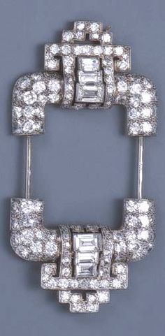 AN ART DECO DIAMOND JABOT BROOCH  Designed as two circular and baguette-cut diamond terminals of geometric design, joined by two jabot pins, circa 1930, 6.4 cm. long, with French assay marks for platinum and gold