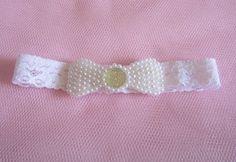 Faixa infantil de elastano com um laço de contas de pérolas brancas e miolo de pedra. As contas plásticas de pérolas são bordadas, não coladas. A circunferência da faixa serve normalmente para bebês a partir de 3 meses até crianças maiores.