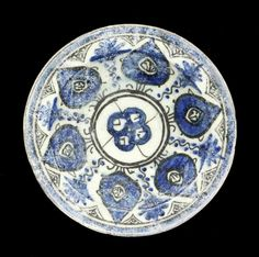 A Mamluk underglaze painted pottery Dish  Egypt or Syria, 14th Century of shallow rounded form on a short foot, decorated in cobalt-blue and black on a white ground under a transparent glaze, the centre with a stylised rosette within two concentric bands, the cavetto with a frieze of six large palmettes with floral sprays and triangular sections above, the outer borders with plain bands, the exterior with radiating lines