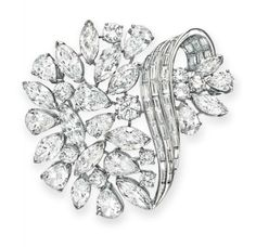 A DIAMOND BROOCH  Designed as a circular, pear and marquise-cut diamond cluster with scrolling baguette-cut diamond detail, mounted in platinum