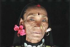 Portrait of hardship and heartbreak, 55-year-old Chanda raised six girls alone after her husband's early death. Her sorrow deepened recently when illness claimed the life of her daughter Kurowa. Yet her adornments defy despair: The vivid hibiscus and 20-rupee note in her ears imply beauty and wealth; a red flash at her hairline recalls her past marriage.
