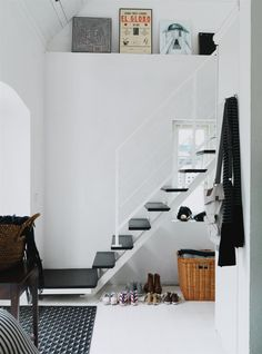 Weightless black & white entry hall. Love the floating black stair treads against the white wall.