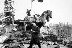 Soviet war photographer Yevgeny Khaldei at Brandenburg Gate, where Red Army soldiers had hoisted a red flag as a sign of victory over Hitler and Nazi Germany (02.05.1945).