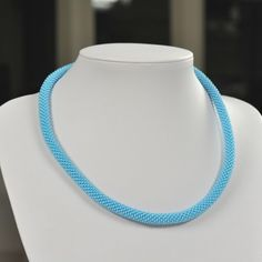 Unique handmade light blue bead necklace made of light blue beads and white thread.