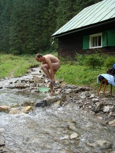 Naked man next gingerbread house in a quiet forest