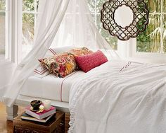 This bedroom has a Moroccan feel with its platform day bed, wood chest and draped fabric canopy. The colors in the pillows are quite summery.