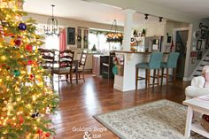 Red and white Christmas kitchen with candle chandelier, diy mantel hood, and white cabinets.