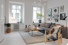 rug, sleek coffee table, couch against wall, gallery wall, warm neutrals, big windows