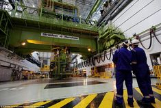 Size matters: Two technicians study the huge fueling machine in the Charge Hall. The fuel is uranium dioxide pellets clad in stainless steel, which produce 1600 megawatts of heat in the reactor