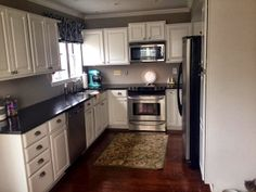 Kitchen, Chandelier, Dark Hard Wood Hand Scraped, Coffee Station, White Cabinets, Black Granite Counter top, Hang curtains high, Cannisters, Kitchen Layout