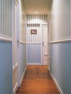 Este recurso ha pertimido romper la monotonía de este corredor, que era muy largo y estrecho.   Un zócalo para acortar. Está pintado de azul celeste y ayuda a restar profundidad, a la vez que la moldura sirve para ensanchar y agrandar visualmente el espacio.