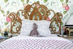 Girls room with wallpaper and ornate bed.