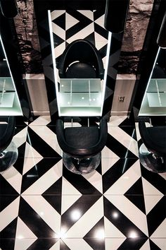 The decor of this modern elegant beauty salon creates a sense of luxury through the use of black and white tile patterns.  The interior design is sophisticated with its use of bronze sheer curtains to create private treatment rooms. Other decor ideas are the use of sleek styling stations giving a boutique hair salon ambience. | #floor | #mirror | #stylingstation |