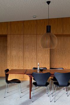 Hans J. Wegner dining table in teak, Arne Jacobsen´s Seven chairs in leather and Secto pendant light by Seppo Koho. Interior from Villa Aarhus by Friis & Moltke.