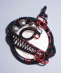 Dramatic black and red wire wrapping contrasts with white shell and gray glass pearls.     The pendant measures approximately 1.5 inches long.    Black cord with a toggle clasp is included; please be sure to select your desired length and clasp color.     $16.00