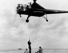 Civilian Rescue.  Joseph Pawlik, captain of the barge aground on Penfield Reef, off Fairfield, CT, is lowered to safety from a Sikorsky R-5 helicopter piloted by Jimmy Viner, the company chief pilot, assisted by Capt. Jack Beighle of the Army Air Force. The Nov. 29, 1945 hoist rescue was the precursor to many thousands of missions to come.
