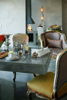 love the classic French furniture with the cool concrete surfaces