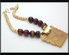 SOO CHOW JADE PENDANT NECKLACE by Sandra Webster A superbly handcrafted and intricately detailed jade pendant hangs from a necklace made of large, natural Soo Chow jade beads and antiqued bovine bone beads. the large jade beads are encased in hand forged bronze bead caps that have a raw silk texture. A portion of Sandra Webster's proceeds, support the Austin Humane Society.