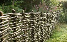 A woven hazel fence adds structure and rustic charm to the garden.