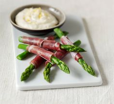 A quick and classic spring canapé of tender green stems wrapped in Parma ham with a light citrus dip