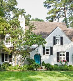 Painted White Brick - Traditional Home, low shrubs in front of house, door color breaks up too much green as do window box flowers