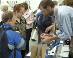 Attendees visited exhibitors to learn about their services. In this picture Joan Sharp (center) escorts Christine (left) as Associate State Librarian for Library Services David Namiotka explains how to use the digital talking machine adapter.