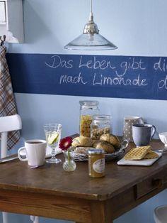 Ein toller Kontrast zum dunkelbraunen Tisch ist die blaue Wand. Das i-Tüpfelchen: ein dunkelblauer Tafelfarbe-Streifen.