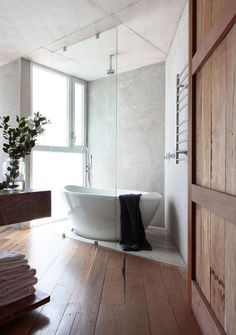 Love the mix of rugged thick wood panels here on the door, floor, bathroom shelves and the stone under and behind the porcelain tub.