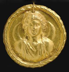 A ROMAN GOLD MEDALLION OF LUNA   CIRCA 3RD-6TH CENTURY A.D.   The sheet disk with a repoussé bust of the moon goddess depicted frontally wearing a sleeveless tunic, her center-parted hair rolled back along the sides of her face and falling along her neck, a crescent moon behind her, the medallion with a raised ribbon border, perforated above and threaded through by a hooked wire