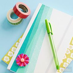 """Everyone could use a journal, especially one as pretty as this. The trick? Washi tape! The decorative tape comes in a ton of colors, patterns, and sizes -- and makes any drab notebook look fresh and new. Make the flower: Adhere five strips of washi tape close together on a piece of cardstock to create """"tape paper"""" for punching. Punch three or four flowers from the tape paper, layer the pieces, and fasten them in the center with a brad. /"""