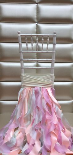 Idea for decorating your wedding ceremony and reception chairs. Frilly ribbon garland chair skirt in candy pastels.