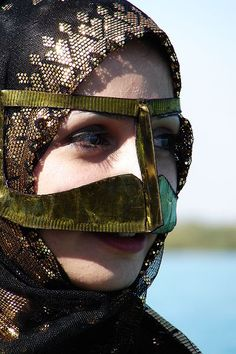Closeup of the Burqa, a golden scarf covering the face, which is part of the traditional Bandari costume of Southern Iran. | © Hamed Saber {Married Women wear it in United Arab Emirates, Oman, Qatar and Arabs of southern Iran and southeastern Turkey. This tradition has almost died out in the newer generations. Older women usually not younger than 50, and those living in rural areas can still be seen wearing them.}