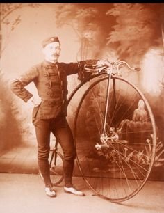 1886 photograph of man with high wheel bicycle. Now those are some fancy riding duds.