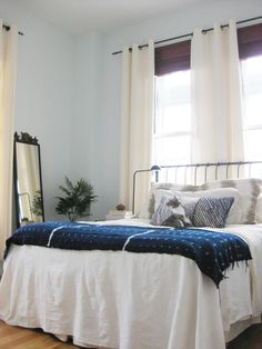 iron bedframe with white comforter, pale blue walls
