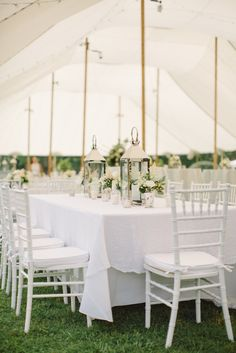 Clean white reception with silver lanterns, mercury glass candles, and mercury glass jars filled with white roses and astilbe
