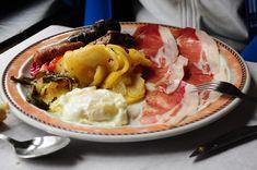 Trocear la patatas peladas en rodajas no muy finas. Trocear la cebolleta en trozos más pequeños. Añadir los dos ingredientes a una sartén con abundante aceite caliente hasta que la patata quede más bien cocida. En una sartén aparte freír los pimientos verdes previamente lavadas, sin pepitas y cortados a trozos medianos. Freír huevos, chorizos,…