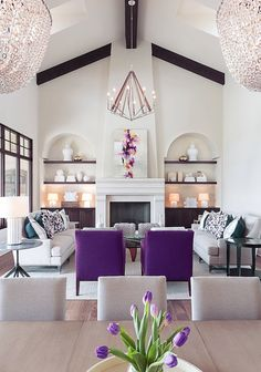 Elegant Transitional style white and purple luxury living room decor with purple armchairs, beautiful formal living room decor with glam chandler and modern fireplace