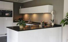 Strak moderne hoogglans witte keuken met zwart werkblad - bij Johan Bos Keukens