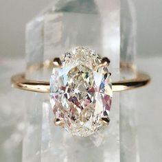 Oval engagement ring with a four prong setting and 14K gold band.