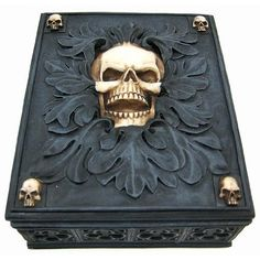 Creepy Gothic Skull Jewelry / Trinket Box by Valet, This beautiful trinket/jewelry box makes a great conversation piece, and makes a great gift for any skull lover. Measuring 2 inches high, 4 inches wide and 5 1/2 inches long, it features an evil-looking skull in the center of the lid, wicked half-skull corners and foliage accents. The interior dimensions are 1 1/4 by 5 by 3 7/8. It's made of cold cast resin.