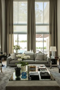 This lovely olive-toned living room is stunning in the combination of the neutral palette and the large, inviting windows