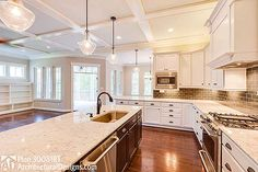 Warm brown floors, white cabinets,   speckled granite, gooseneck faucet and brown backsplash