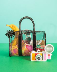 A clear bag is picture-perfect when filled with super-saturated accessories: Black clear satchel and printed beach towel, H & M, Berwick 1980 sunglasses in White Opaque, available at Artsee Eyewear (NYC); La Sardina camera with flash, Lomography. | Photo by Ingalls Photo